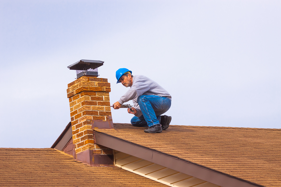 man fixing house chimney