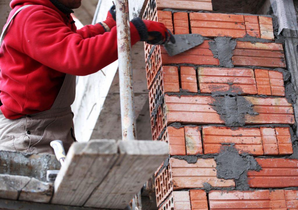 man making house walls
